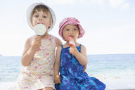 Female toddler and sister wearing sunhats eating ice lollies on beach - CUF30110