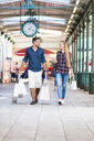 Young couple strolling with shopping bags in arcade - CUF30143