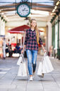 Full length front view of young woman carrying shopping bags looking away smiling - CUF30149