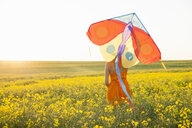 Rear view of mid adult woman in canola field arm raised holding kite - CUF30152