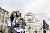 Lesbian couple holding digital camera hugging in front of church, Piazza Santa Maria, Novella Florence, Tuscany, Italy - CUF30158