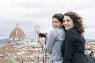 Lesbian couple taking photo of Florence Cathedral and Giotto's Campanile looking over shoulder smiling, Florence, Tuscany, Italy - CUF30161