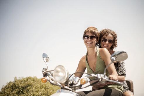 Portrait of two women sitting on moped - CUF30188