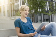 Happy young woman using digital tablet on city stairway - CUF30206