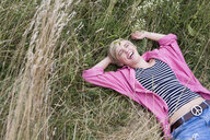 Young woman lying in long grass laughing - CUF30212