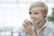 Young woman drinking takeaway coffee in city - CUF30218