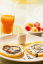High angle view of pancake and chocolate sauce breakfast with fruit salad and orange juice - CUF30416