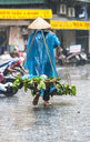 Woman carrying baskets with grocery in heavy rain in the old quarters of Hanoi, Vietnam - CUF30455