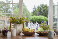 Kitchen table with breakfast foods, family in garden behind, focus on table - CUF30508