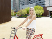Young woman on bicycle, Southbank, Melbourne, Australia - CUF30637