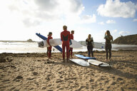 Group of surfers standing on beach, holding surfboards, rear view - CUF30658