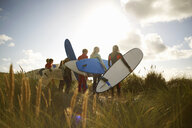 Group of surfers standing on beach, holding surfboards, rear view - CUF30661