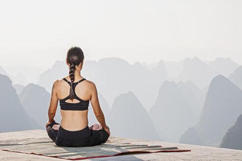 Rear view of woman in yoga lotus pose above limestone mountains, Yangshuo, Guangxi Zhuang, China - CUF30664