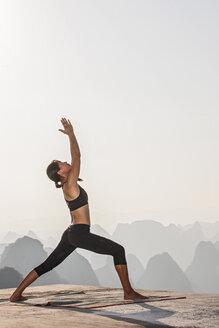 Side view of woman in yoga warrior pose above limestone mountains, Yangshuo, Guangxi Zhuang, China - CUF30667