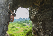 Male climber at treasure cave in Yangshuo, Guangxi Zhuang, China - CUF30673