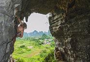 Male climber at treasure cave in Yangshuo, Guangxi Zhuang, China - CUF30673