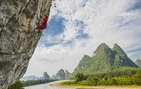 Side view of male climber at Riverside crag in Yangshuo, Guangxi Zhuang, China - CUF30682