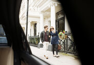 Car window view of young couple strolling on street, London, England, UK - CUF30775