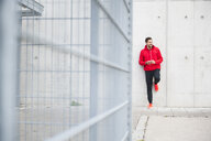Young male runner leaning against wall listening to earphone music - CUF30802