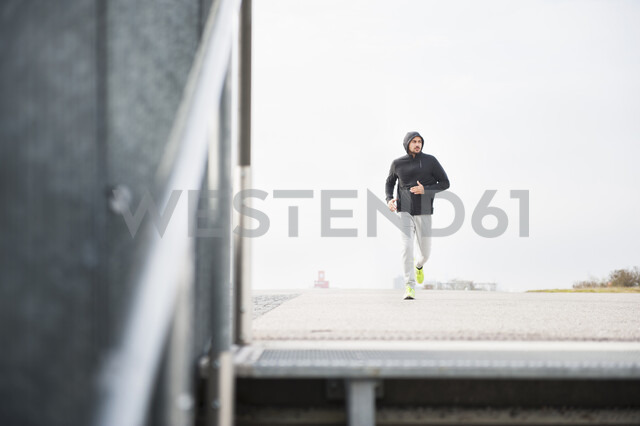 Young male runner running in sport arena - CUF30808