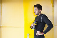 Young male runner leaning against yellow wall taking a break - CUF30826