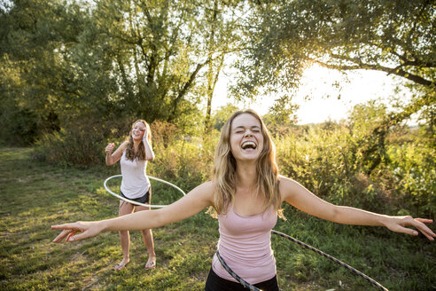 Two young girls in rural environment, fooling around, using hula hoops, - CUF30841