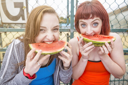 Young women eating watermelon beside sports ground, London, UK - CUF30883