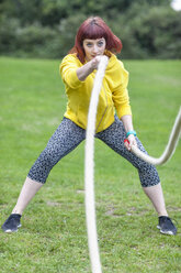 Young woman pulling rope on field - CUF30892