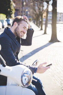 Stylish young man sitting on moped with smartphone - CUF31141