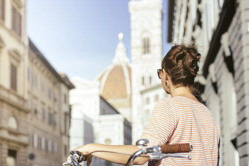 Rear view of mid adult woman holding bicycle looking at Duomo Cathedral, Florence, Italy - CUF31171