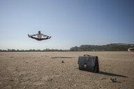 Mid adult businessman jumping mid air at beach - CUF31174