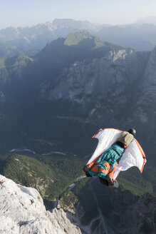 Male BASE jumper wingsuit flying from mountain, Dolomites, Italy - CUF31204