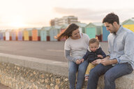 Young family sitting on beach wall - CUF31249