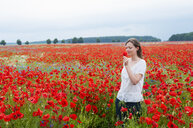 Mid adult woman walking through poppy field, smelling poppy in hand - CUF31252