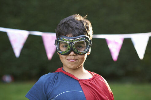 Portrait of boy wearing goggles and cape, looking at camera - CUF31297