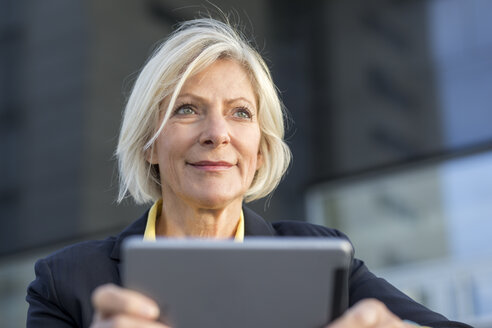 Portrait of smiling senior businesswoman with tablet outdoors - FMKF05139