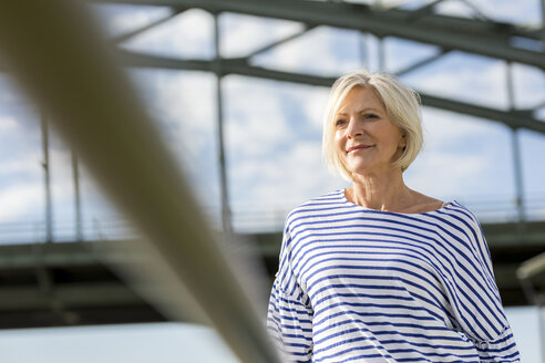 Portrait of smiling senior woman at a bridge - FMKF05148