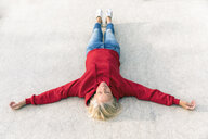 Senior woman wearing red hoodie lying on the ground outdoors - FMKF05154