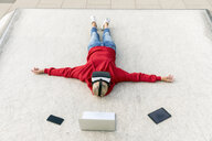 Senior woman lying on the ground wearing VR glasses next to mobile devices - FMKF05157