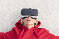 Senior woman lying on the ground wearing VR glasses - FMKF05160