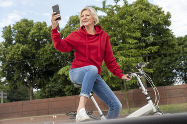 Senior woman with city bike using cell phone - FMKF05163