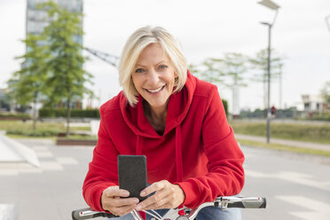 Portrait of smiling senior woman with city bike and cell phone - FMKF05166