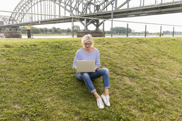 Senior woman sitting on a dike using laptop - FMKF05169