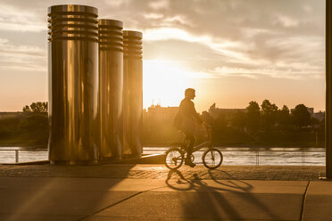 Senior woman riding city bike at the riverside at sunset - FMKF05175