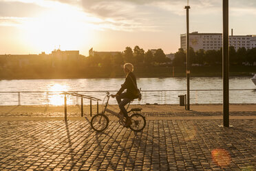 Senior woman riding city bike at the riverside at sunset - FMKF05178