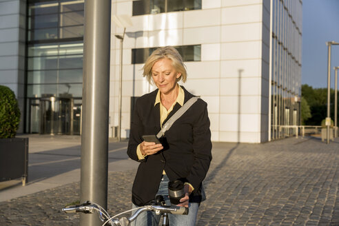 Senior woman with city bike and takeaway coffee using cell phone - FMKF05181