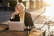 Smiling senior businesswoman using laptop in the city at sunset - FMKF05184