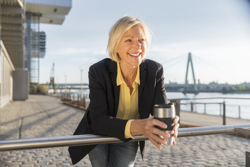 Happy senior businesswoman with takeaway coffee at the riverside - FMKF05187