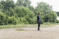Businessman standing in remote landscape - UUF14076