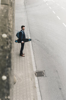Businessman carrying skateboard standing at the street - UUF14088